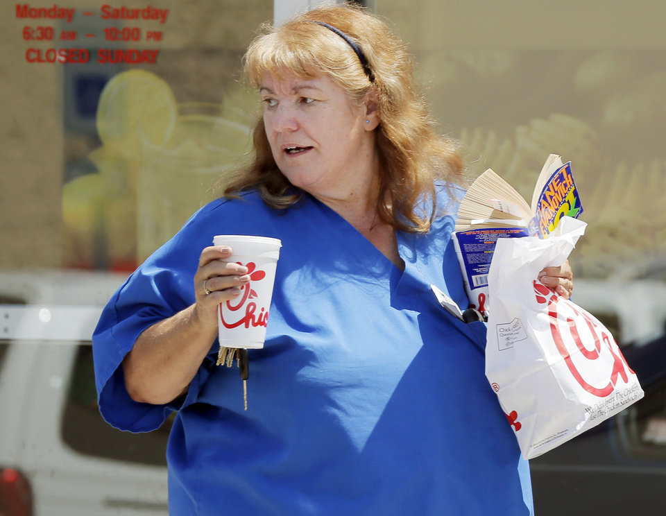 Photo - Letha Manous leaves the Chick-fil-A at 6201 N May with her lunch in a to-go bag during Chick-fil-A Appreciation Day in Oklahoma City, Wednesday, Aug. 1, 2012. Manous said she waited about 30 minutes in line. Photo by Nate Billings, The Oklahoman