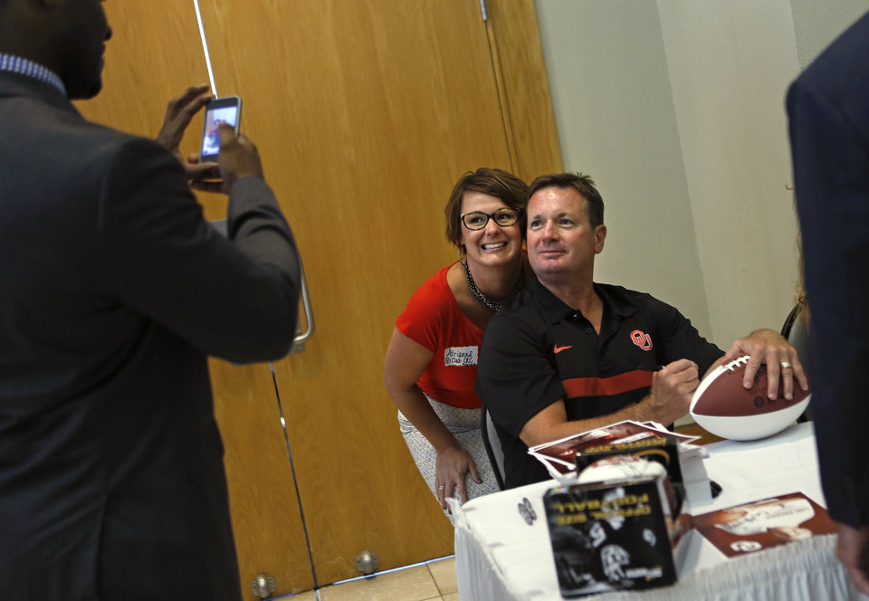 Photo - UNIVERSITY OF OKLAHOMA / OU / COLLEGE FOOTBALL: Adrianne Covington Graham of Oklahoma City has her picture taken with Oklahoma football coach Bob Stoops during the Sooner Caravan stop at the National Cowboy & Western Heritage Museum  in Oklahoma City, Wednesday, August 1, 2012. Photo by Bryan Terry, The Oklahoman