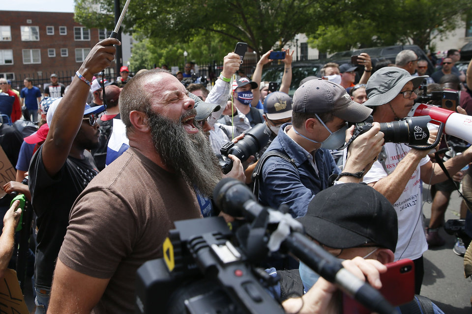 Photo - A Donald Trump supporter shouts at protesters before a President Donald Trump rally at the BOK Center in Tulsa, Okla., Saturday, June 20, 2020. [Bryan Terry/The Oklahoman]