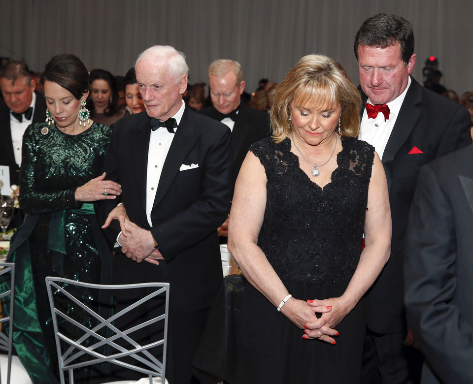 Photo - Former Gov. Mary Fallin and husband Wade Christensen pray next to former Gov. Frank Keating and wife Cathy Keating during the inaugural ball for Gov. Kevin Stitt at the Cox Convention Center in Oklahoma City, Monday, Jan. 14, 2019. Photo by Nate Billings, The Oklahoman
