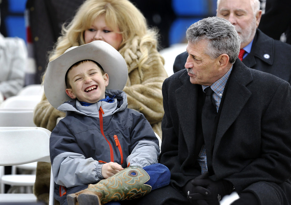 Photo - Stran Talley, 8, laughs while sitting with  his grandfather, Rep. John Talley as the pair wait for the inauguration ceremony for Kevin Stitt to begin. The elder Talley is beginning his first term in the House of Representatives, serving District 33. Stran is a third grade student at Sangre Elementary School in Stillwater. It was the first time for both Talleys to attend an inauguration.  Stitt was sworn in as Oklahoma's 28th governor by Supreme Court Chief Justice Noma Gurich on Monday, Jan. 14, 2019. Photo by Jim Beckel, The Oklahoman.