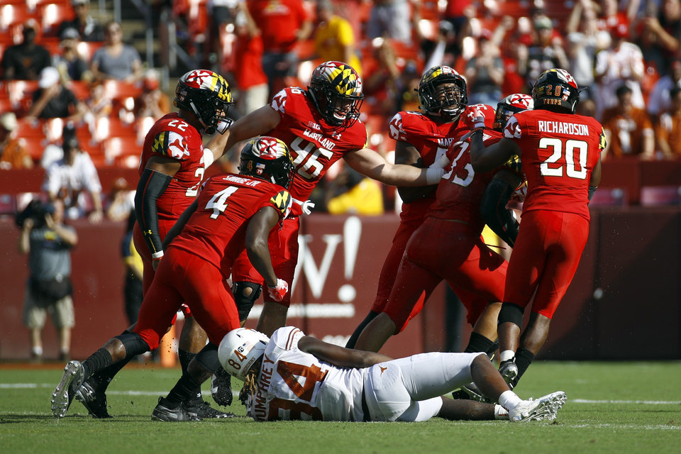 Photo -  Maryland players celebrate in front of Texas wide receiver Lil' Jordan Humphrey after Maryland linebacker Tre Watson, second from right, intercepted a pass intended for Humphrey in the second half of Saturday's game in Landover, Md. Maryland won 34-29. [AP PHOTO]