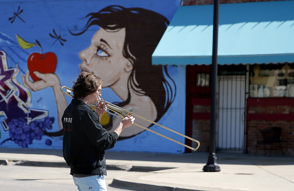 Photo - Christian Pearson plays the trombone in an empty the Plaza District in Oklahoma City, Friday, April 10, 2020. [Sarah Phipps/The Oklahoman]