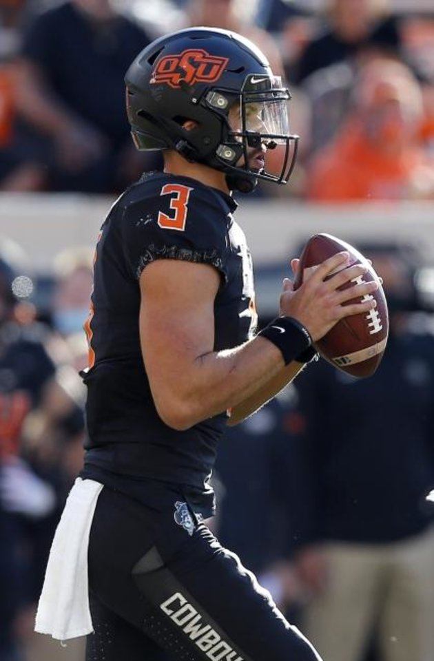 Photo -  Oklahoma State's Spencer Sanders looks to throw a pass in the second quarter against Texas on Saturday. [SARAH PHIPPS/THE OKLAHOMAN]