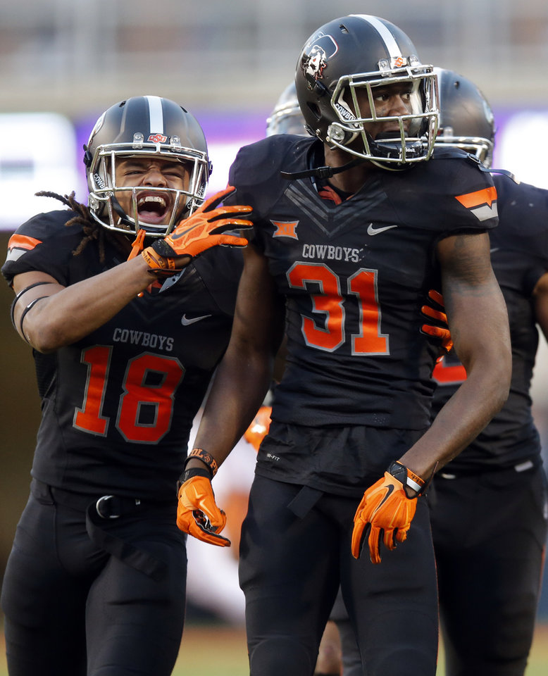 Photo - Oklahoma State's Tre Flowers (31) and Ramon Richards (18) celebrate a Flowers touchdown during the college football game between the Oklahoma State Cowboys (OSU) and TCU Horned Frogs at Boone Pickens Stadium in Stillwater, Okla., Saturday, Nov. 7, 2015. Photo by Sarah Phipps, The Oklahoman