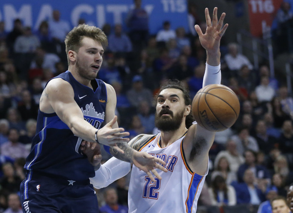 Photo - Dallas Mavericks forward Luka Doncic (77) passes in front of Oklahoma City Thunder center Steven Adams (12) in the first half of an NBA basketball game in Oklahoma City, Monday, Dec. 31, 2018. (AP Photo/Sue Ogrocki)