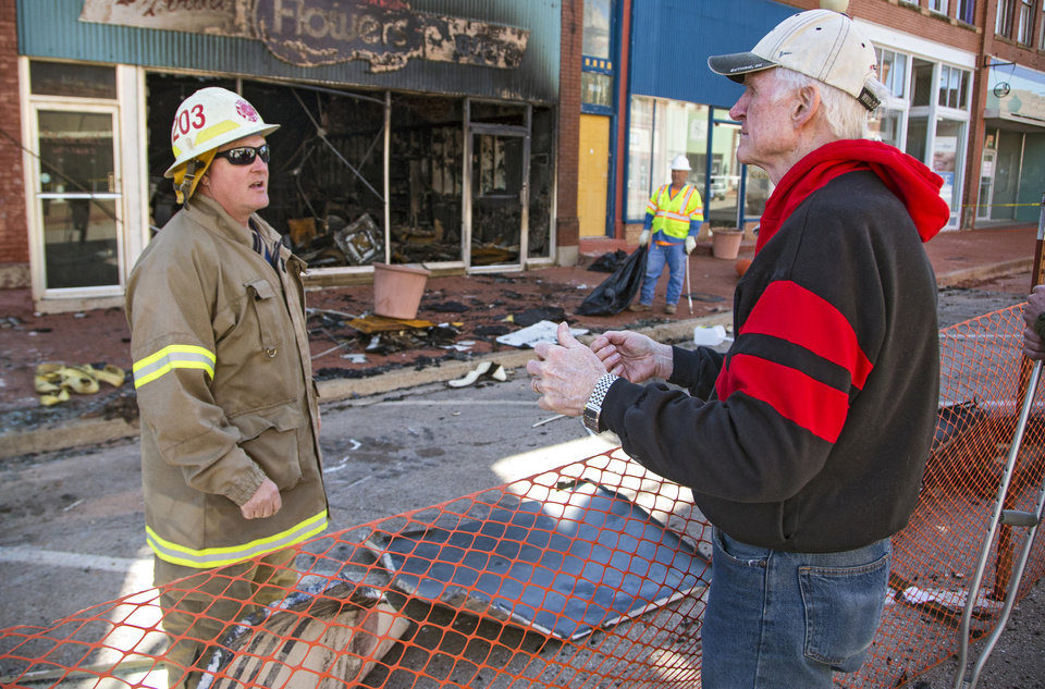 Photo - Fiddle player Byron Berline, right, talks to a Guthrie firefighter as they try to retrieve a safe from the damage of a fire that destroyed Berline's fiddle shop in Guthrie, Okla. on Monday, Feb. 25, 2019. The fire on Saturday destroyed two businesses in historic downtown Guthrie.   Photo by Chris Landsberger, The Oklahoman