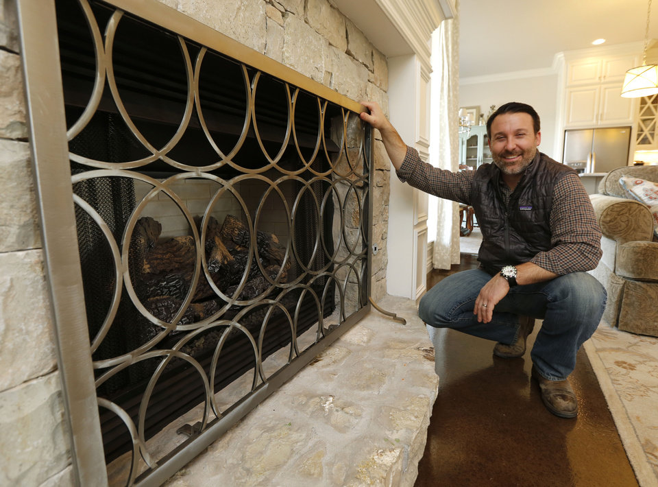 justin hodges owner of urban ironcraft shows a fireplace grate for his home in
