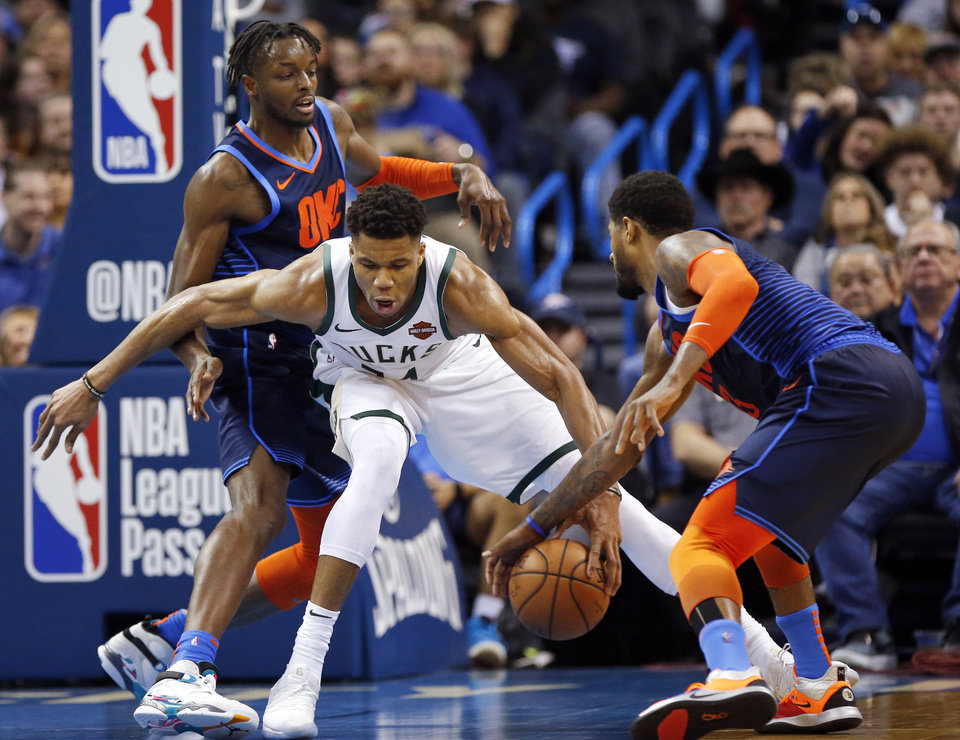 Photo - Oklahoma City's Paul George (13) steals the ball from Milwaukee's Giannis Antetokounmpo (34) as Oklahoma City's Jerami Grant (9) defends in the third quarter during an NBA basketball game between the Milwaukee Bucks and the Oklahoma City Thunder at Chesapeake Energy Arena in Oklahoma City, Sunday, Jan. 27, 2019. Oklahoma City won 118-112. Photo by Nate Billings, The Oklahoman