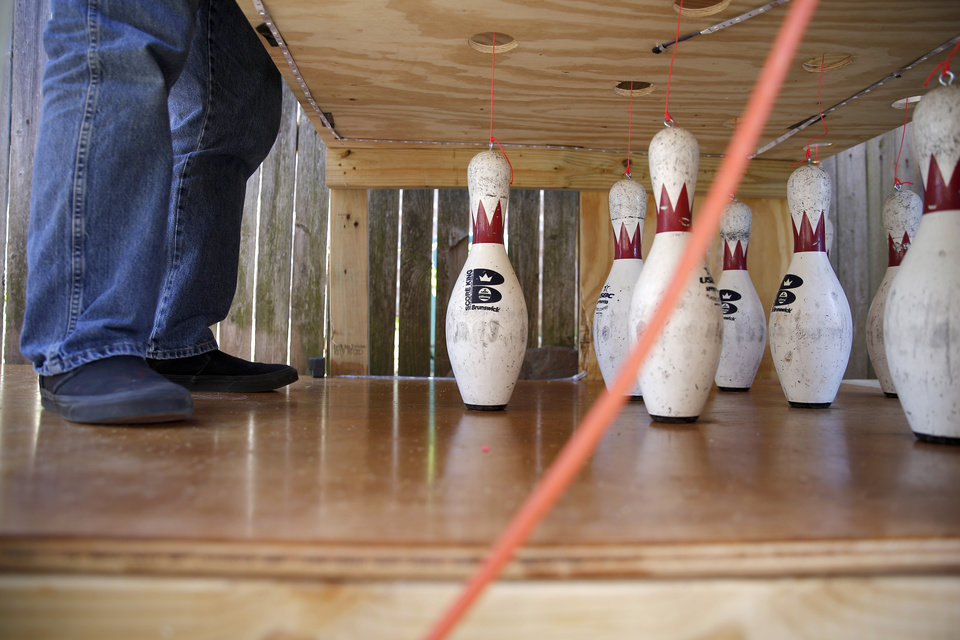 Photo - Heath Jones repairs a line attached to a bowling pin on a bowling lane in the backyard of his Oklahoma City home, Tuesday, April 21, 2020. Health Jones and his son Eric built a bowling lane in their backyard so that Eric, a competitive bowler, could continue to bowl while bowling alleys are closed.. [Bryan Terry/The Oklahoman]