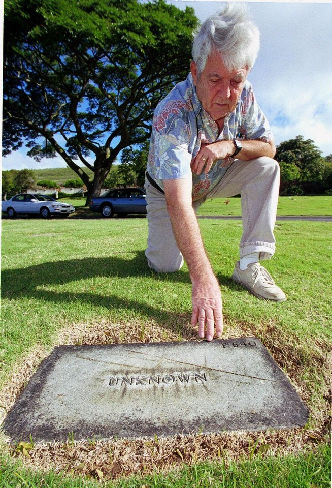 Photo - Raymond Emory in 1999 points to the tombstone of the first casualty to be recorded from the attack on Pearl Harbor, at the National Memorial Cemetery of the Pacific in Pearl Harbor, Hawaii. Buried beneath the vast lawn at the cemetery are the remains of 647 unidentified servicemen killed on Dec. 7, 1941, during the Japanese attack on Pearl Harbor. The Army has some information that would make the markers more specific, but it refuses to do so. Emory has waged an eight-year battle to make the markers more specific. AP Photo  RONEN ZILBERMAN  AP
