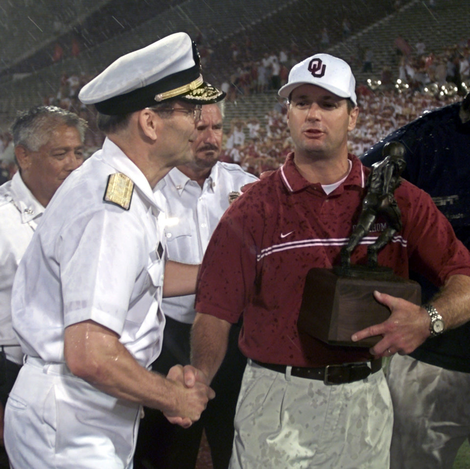 Photo - University of North Carolina (UNC) vs OU college football in Norman, OK Saturday Aug 25, 2001.   Bob Stoops accepts the trophy for winning the Hispanic College Fund game as the rain begins to come down and fans scatter.  Staff photo by Steve Sisney