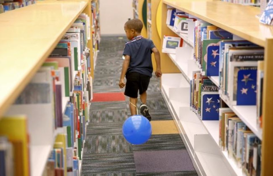 Photo -  JaJa Harris looks at books in the children's area of the library. [Sarah Phipps/The Oklahoman]