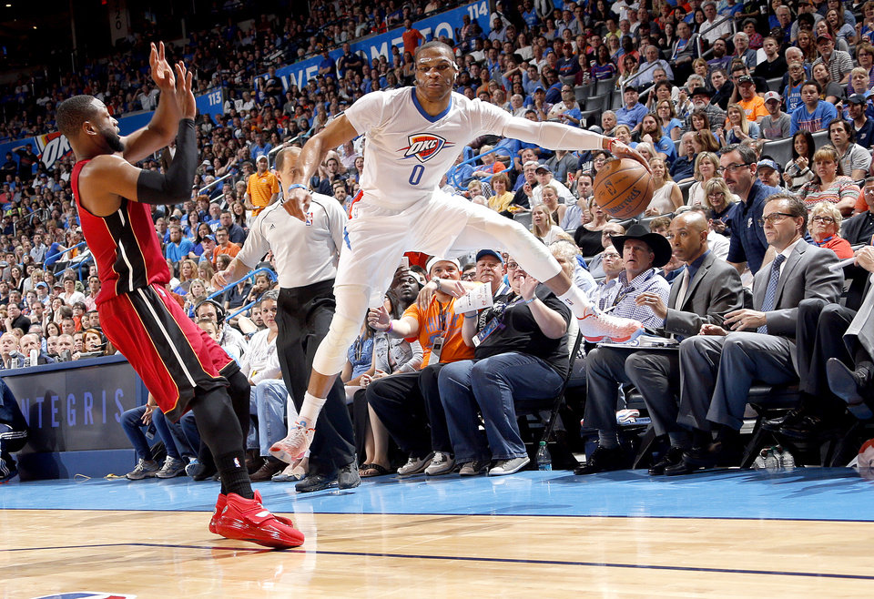 Photo - Oklahoma City's Russell Westbrook (0) saves the ball from going out of bounds as Miami's Dwyane Wade (3) defends during the NBA basketball game between the Oklahoma City Thunder and the Miami Heat at the Chesapeake Energy Arena in Oklahoma City, Sunday, March 22, 2015. Photo by Sarah Phipps, The Oklahoman