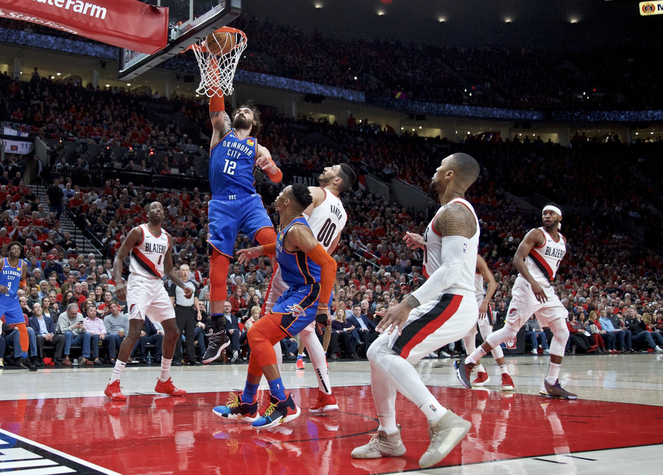 Photo - Oklahoma City Thunder center Steven Adams, left, dunks over Portland Trail Blazers center Enes Kanter during the first half of Game 2 of an NBA basketball first-round playoff series Tuesday, April 16, 2019, in Portland, Ore. (AP Photo/Craig Mitchelldyer)