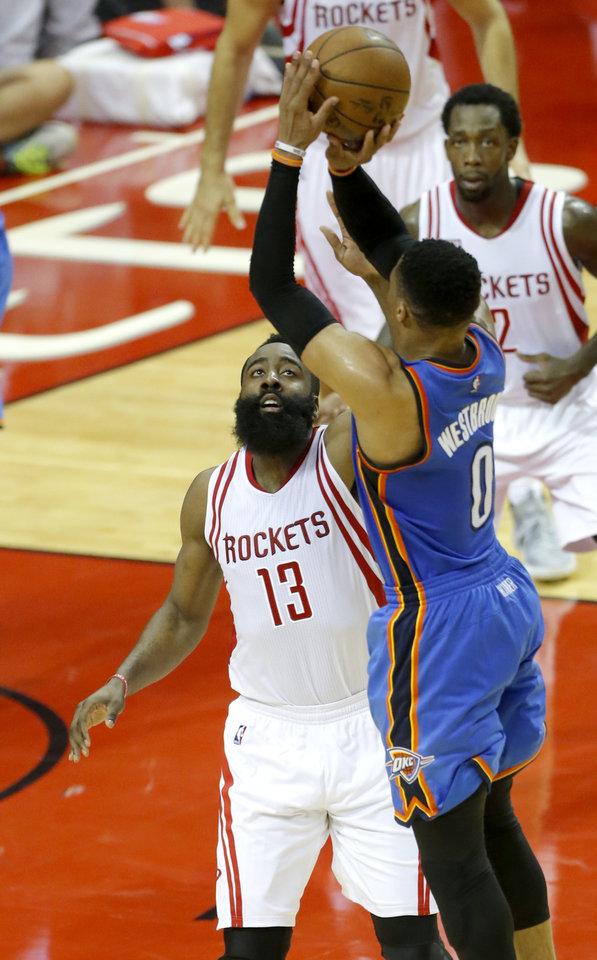 Photo - Oklahoma City's Russell Westbrook (0) shoots over Houston's James Harden (13) during Game 2 in the first round of the NBA playoffs between the Oklahoma City Thunder and the Houston Rockets in Houston, Texas,  Wednesday, April 19, 2017.  Photo by Sarah Phipps, The Oklahoman