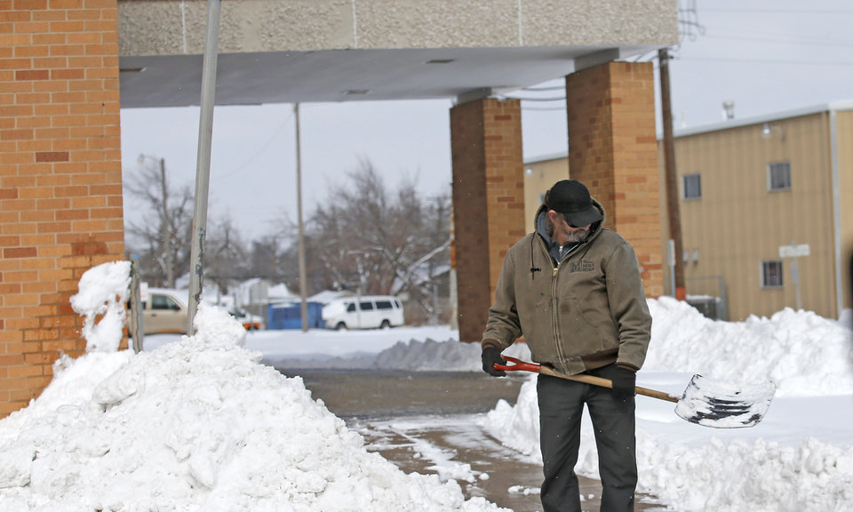 Photo - A man shovels a sidewalk in Oklahoma City, Wednesday, Feb. 17, 2021. [Sarah Phipps/The Oklahoman]