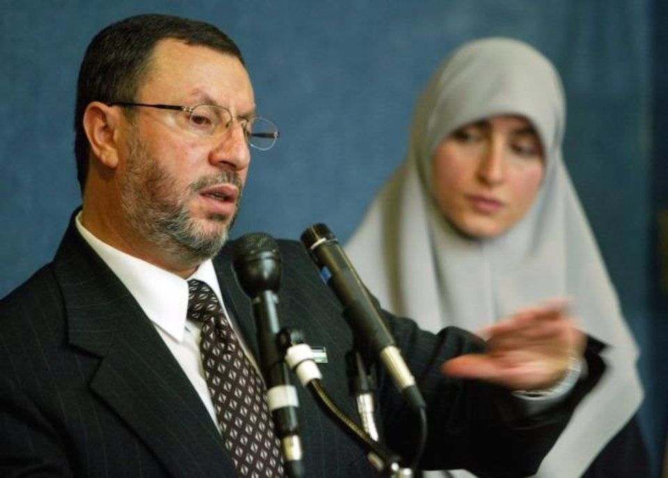 Photo -  Abdelhaleem Ashqar, left, with his wife Asma, right, meets reporters at the National Press Club in 2004.  [Pablo Martinez Monsivais/AP FILE PHOTO]