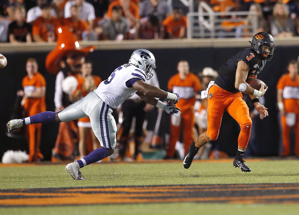 Photo - Oklahoma State's Spencer Sanders (3) gets by Kansas State's Da'Quan Patton (5) in the second quarter during the college football game between the Oklahoma State Cowboys and the Kansas State Wildcats at Boone Pickens Stadium in Stillwater, Okla., Saturday, Sept. 28, 2019. [Sarah Phipps/The Oklahoman]