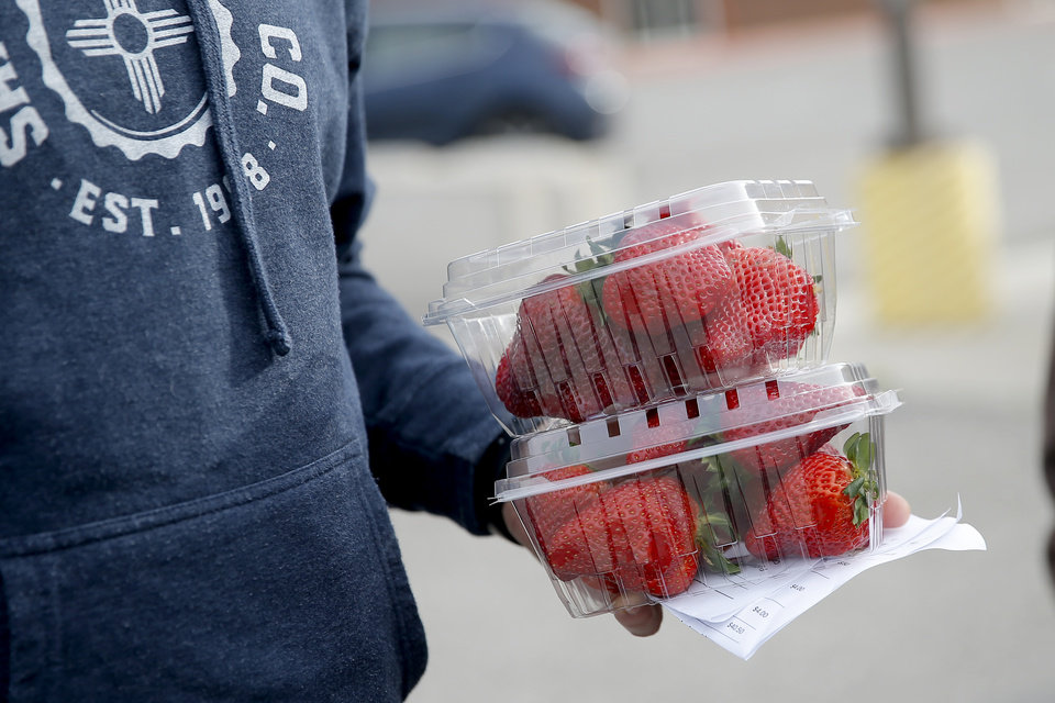 Photo - A customer holds his order of strawberries from The Farm on Fishmarket at the Cleveland County Fairgrounds in Norman, Okla., Saturday, March 21, 2020. The weekly Norman Farm Market was closed to walk up business but customers were able to pick up orders placed in advance. [Bryan Terry/The Oklahoman]
