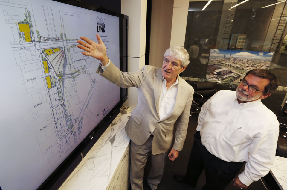Photo -  Bud Miles, left, and Dennis Wells look over plans for a proposed park over I-235 from the Miles Associates offices. [Photo by Paul Hellstern, The Oklahoman]