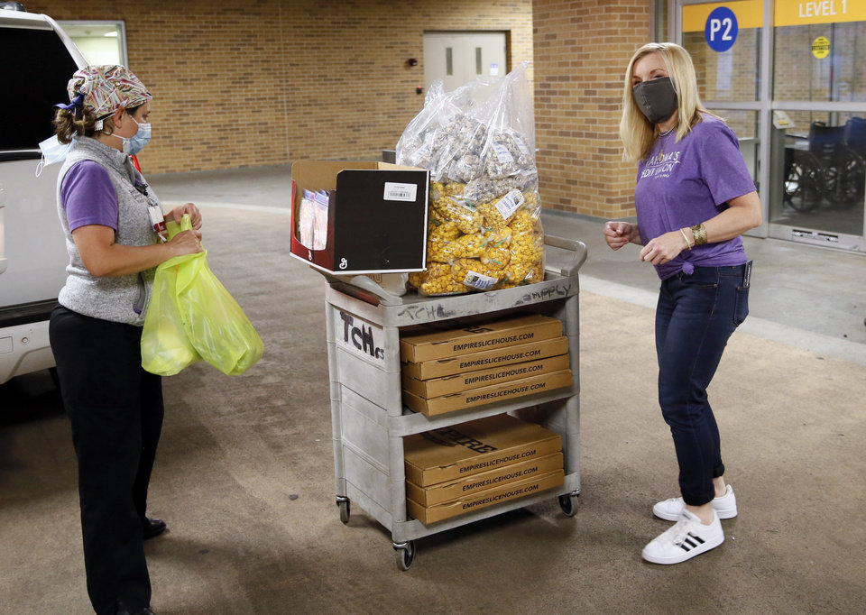 Photo - Nurse practitioner Danielle Briseno, left, looks at a cart of pizza, popcorn and healthcare mask extender straps while talks to Lori Ford with Oklahoma's Credit Union outside the emergency room at The Children's Hospital in Oklahoma City, Sunday, April 26, 2020. Oklahoma's Credit Union purchased pizza from Empire Slice House and popcorn from Oklahoma Gourmet Popcorn for a popcorn and pizza party for night shift healthcare workers at the emergency room. The hospital also received healthcare mask extenders manufactured by entrepreneurs Ian and Hailey McDermid, owners of The Pump Bar and The Bunker Club. [Nate Billings/The Oklahoman]