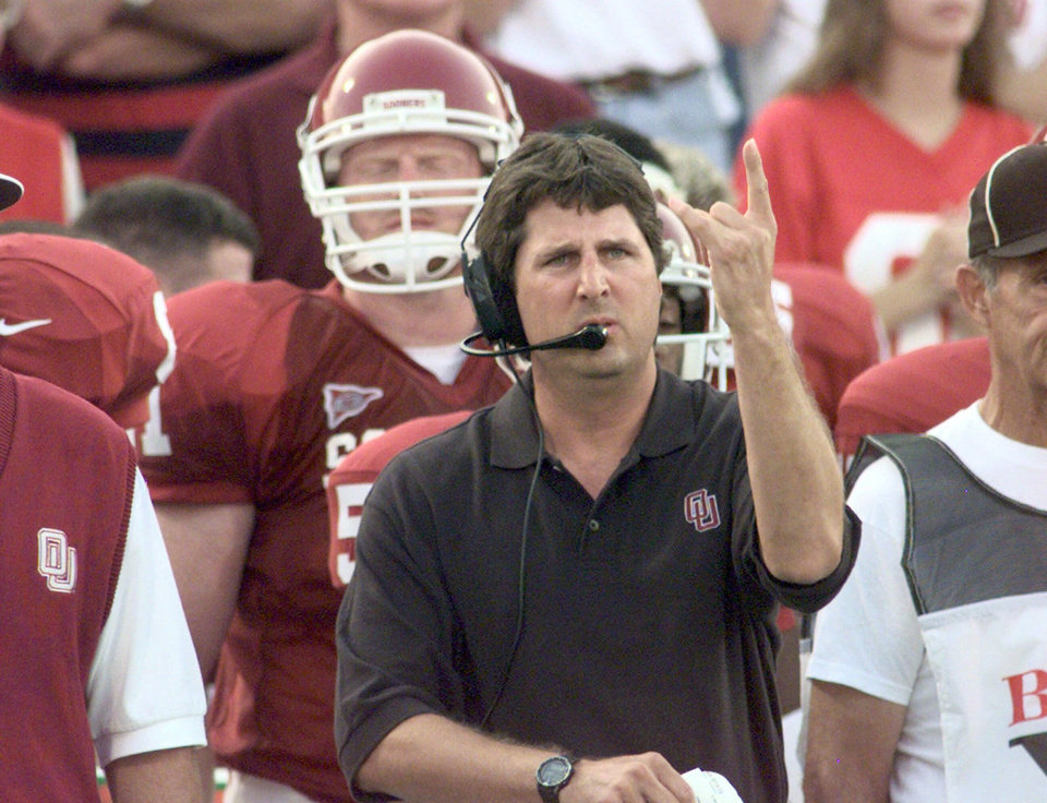 Photo - FILE -- OU college football offensive coordinator Mike Leach signals to quarterback Josh Heupel during the Sooners' game against Indiana State in Norman, Okla., in this September 11, 1999 photo.  No. 19 Oklahoma hopes to build on the freewheeling offense Leach installed as coordinator last season, when the Sooners improved from 101st to 11th nationally in total offense. (AP Photo/Jerry Laizure)
