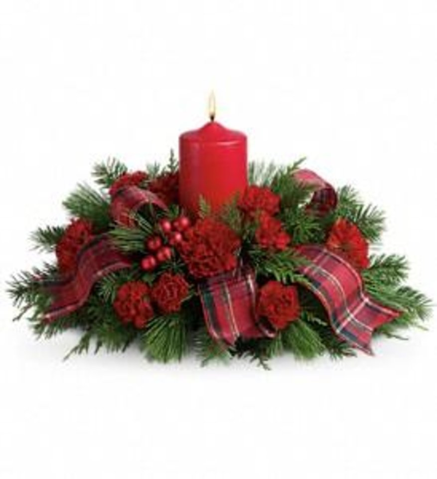 Photo - Festive red carnations, shiny ornament balls, winter greens, an elegant pillar candle and red taffeta ribbon make this a charming celebration of the season - seen at Cheever's Flowers.
