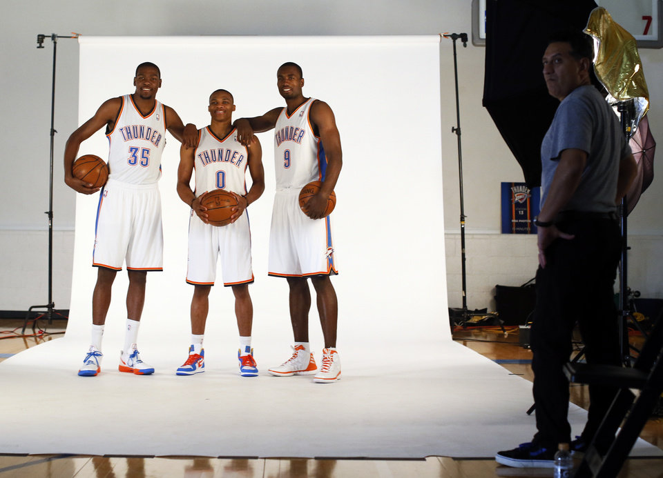 Photo - From left, Kevin Durant, Russell Westbrook and Serge Ibaka have their picture taken during media day for the Oklahoma City Thunder NBA basketball team at the Thunder Events Center in Oklahoma City, Monday, Oct. 1, 2012.  Photo by Nate Billings, The Oklahoman