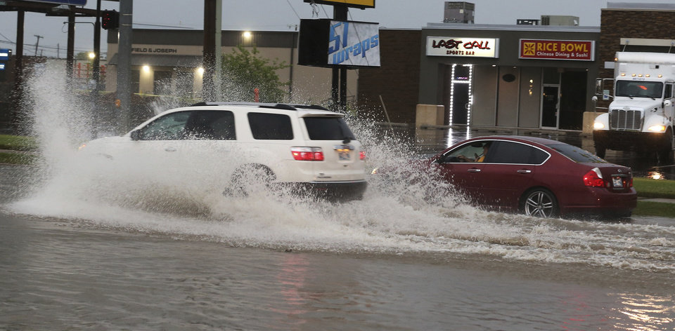 Photo - A car is stranded in high water after rain flooded the street after storms near 43rd and S. Sheridan in Tulsa, Okla., Tuesday, May 21, 2019. (Tom Gilbert/Tulsa World via AP)