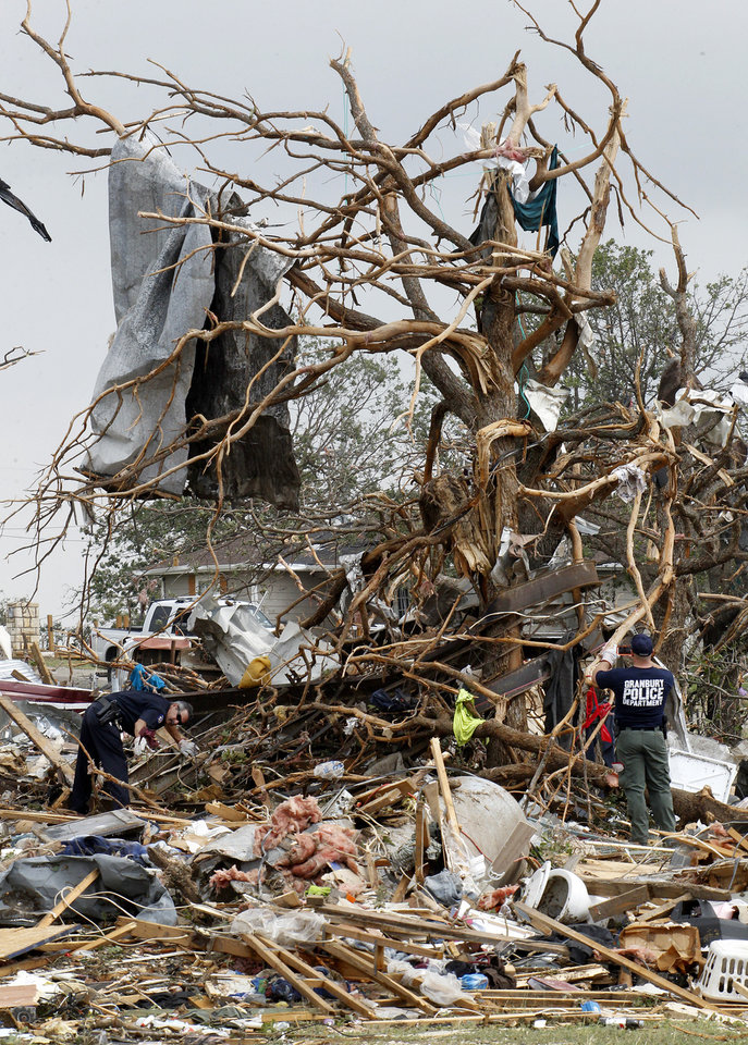 Photo - Searchers working the Rancho Brazos neighborhood in Granbury , Texas, look for unaccounted residents, Thursday, May 16, 2013. A rash of tornadoes slammed into several small communities in North Texas overnight, leaving at least six people dead, dozens more injured and hundreds homeless.  (AP Photo/The Fort Worth Star-Telegram, Paul Moseley)  MAGS OUT; (FORT WORTH WEEKLY, 360 WEST) ORG XMIT: TXFOR110