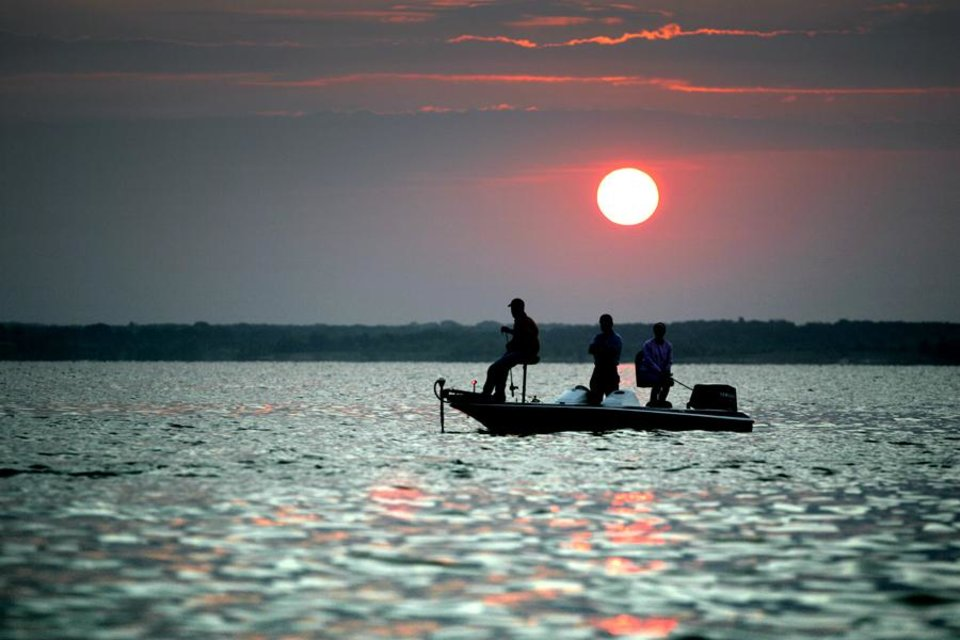 Photo -  BOATS, STRIPER FISHING: A boat  floats on Lake Texoma in Oklahoma as the sun rises, Thursday, July 14, 2005. By Bryan Terry/The Oklahoman ORG XMIT: KOD