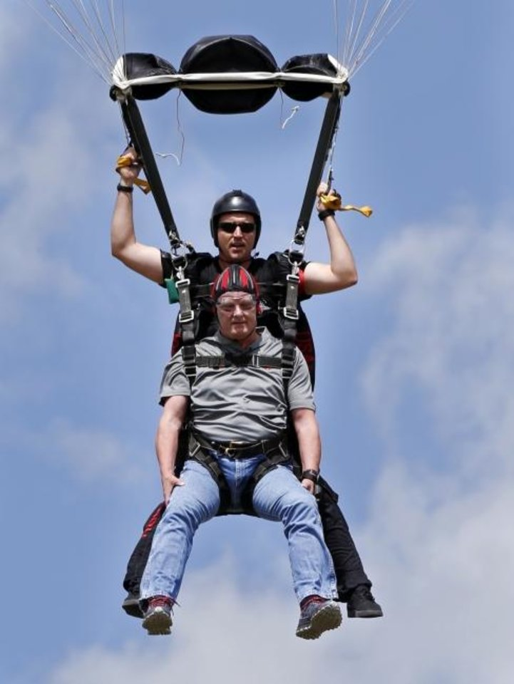 Photo -  OU President Jim Gallogly makes a tandem parachute jump with Sgt. 1st Class Sean O'Toole of the U.S. Army Special Operations Command Parachute Demonstration Team, the Army Black Daggers, as a warm-up to the OU versus Army football game on Sept. 20.  [Steve Sisney/The Oklahoman]