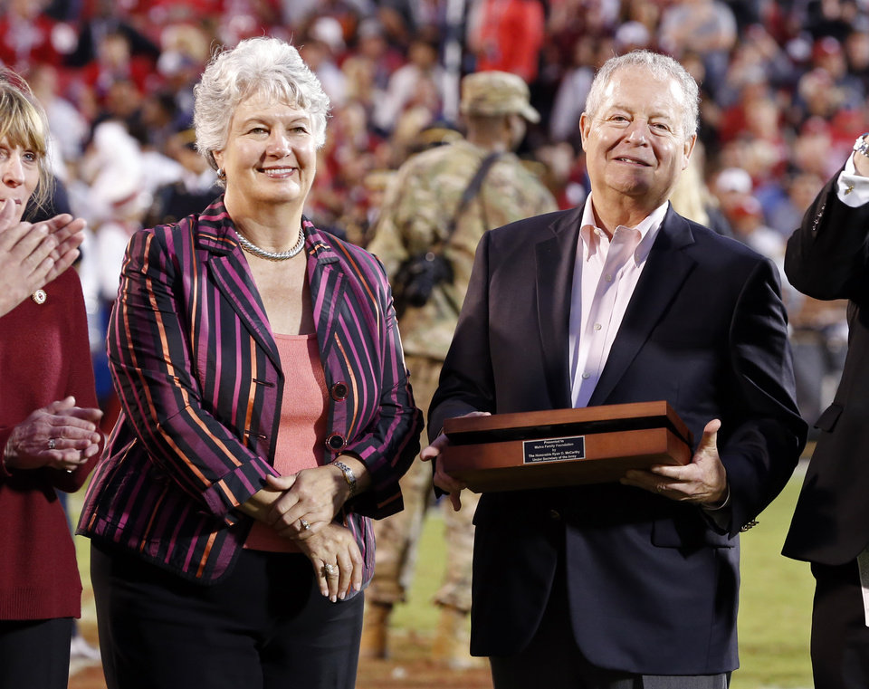 Photo - Miriam and James Mulva of Green Bay, Wisconsin receive a gift as President James L. Gallogly announced their gift of $20 million at half-time of a college football game between the University of Oklahoma Sooners (OU) and the Army Black Knights at Gaylord Family-Oklahoma Memorial Stadium in Norman, Okla., on Saturday, Sept. 22, 2018. Photo by Steve Sisney, The Oklahoman