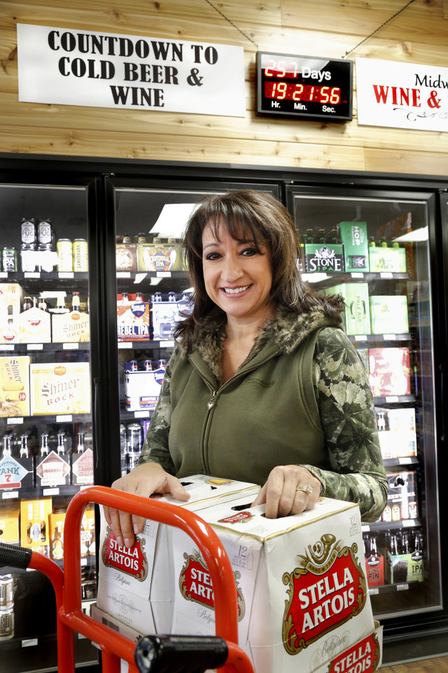 Photo -  Lisa Newport stocks new beer coolers at Midwest Wine and Spirits in Midwest City.