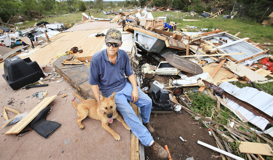 Photo - Charles Taylor, 37, sits Wednesday with his dog, Sissy, in what used to be his living room before a tornado destroyed his mobile home near Earlsboro. Taylor  was in his truck headed home  and got trapped  as the tornado went past. He was not injured.