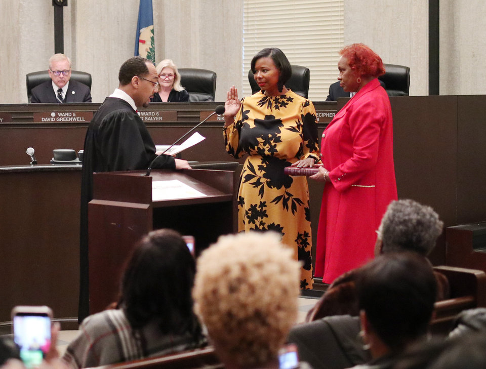 Photo - U.S. Magistrate, Judge Bernard M. Jones swears in Nikki Nice as her mother, Roberta Swanegan, holds the Bible, as new Ward 7 Oklahoma City Councilwoman, Monday, November 19, 2018.  Photo by Doug Hoke, The Oklahoman