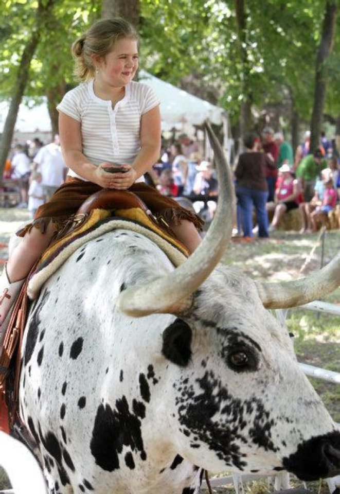 Photo - Lillie Fuller, 5, has her photo taken while riding a longhorn bull at the 2010 Chuck Wagon Gathering and Children's Cowboy Festival at the National Cowboy & Western Heritage Museum. Oklahoman Archive photo by Paul Hellstern  PAUL HELLSTERN