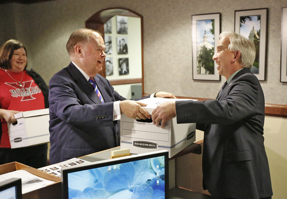 Photo - University of Oklahoma President David Boren, left, delivers the first box of more than 300,000 signatures to launch the Yes for 779 campaign, to Oklahoma Secretary of State Chris Benge at the State Capitol in Oklahoma City, Thursday April 21, 2016. Photo By Steve Gooch, The Oklahoman