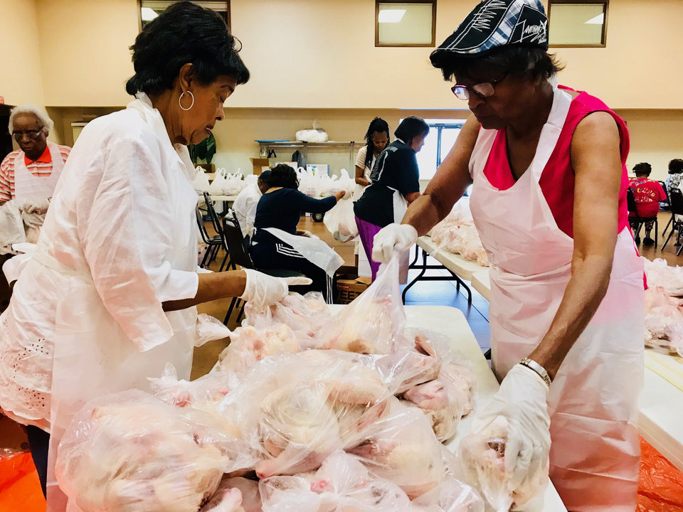 Photo -  Fairview Baptist Church members Shirley Townsend and Jean Fisher place chickens into bags to be distributed as part of the National Baptist Convention's food giveaway Friday at the church, 1700 NE 7. [Photo by Carla Hinton, The Oklahoman]