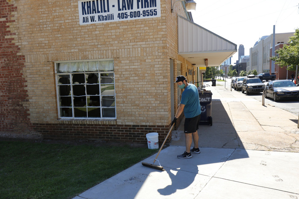 Photo - A man sweeps up glass on the sidewalk out front of Khalili Law Firm on Shartel across from the Oklahoma County Jail Damage from Saturday night protest in downtown Oklahoma City, Sunday, May 31, 2020. [Doug Hoke/The Oklahoman]