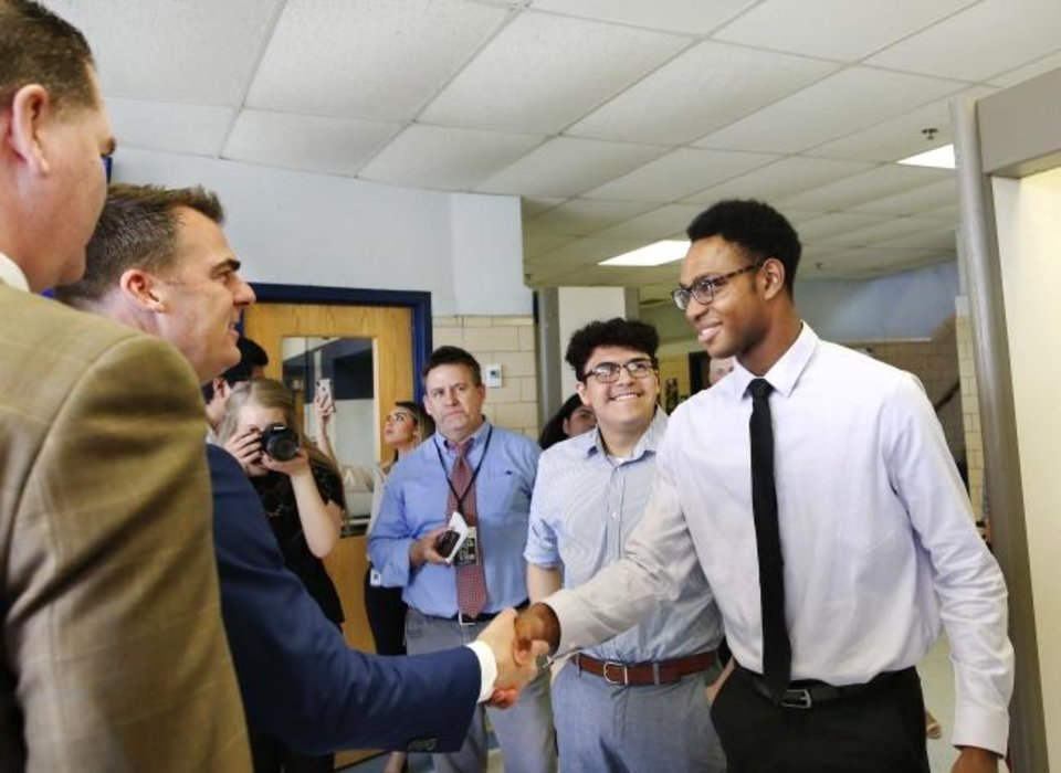 Photo -  De'Angelo Chandler and fellow senior Kevin Palomino welcome Gov. Kevin Stitt as he tours Southeast High School on Wednesday afternoon. At left is Oklahoma City Schools Superintendent Sean McDaniel. Photo by [Jim Beckel photos/The Oklahoman]