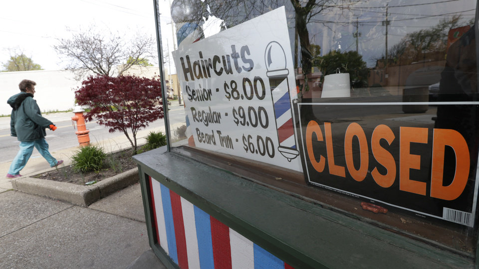 Photo -  A woman walks past a closed barber shop May 6 in Cleveland. [Tony Dejak/Associated press file photo]