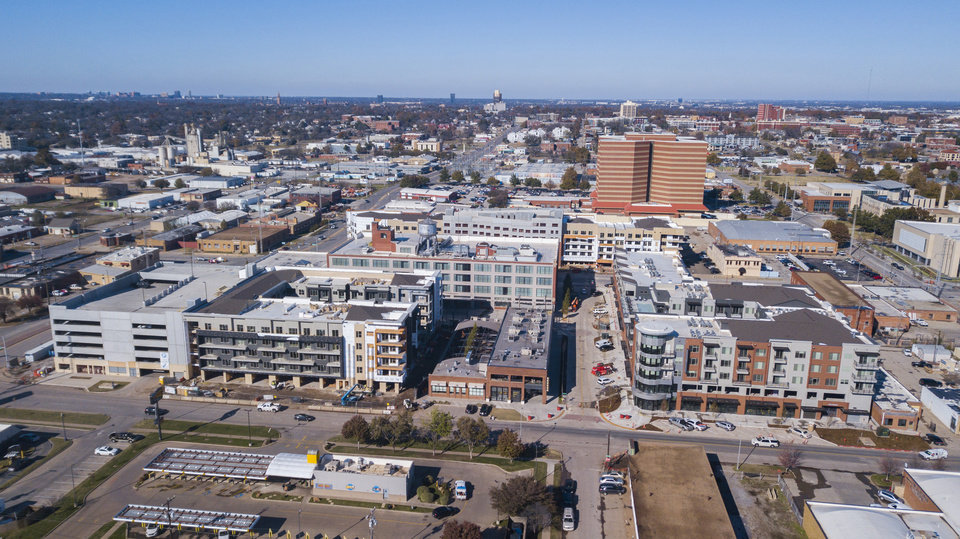 Photo -  The $80 million West Village apartments and retail can be seen surrounding the 21c Museum Hotel and The Jones Assembly in this drone shot looking north across Sheridan Avenue and just east of Classen Boulevard. [Photo by Dave Morris, The Oklahoman]
