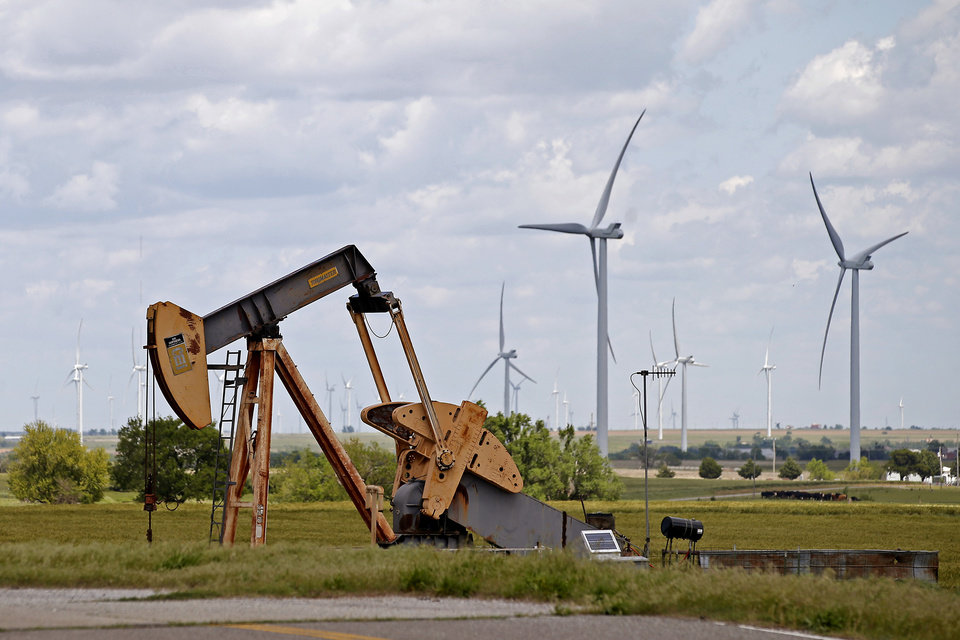 Photo - File: Wind turbines behinf a pump jack are seen just east of Okarche. Photo by Bryan Terry, The Oklahoman archives