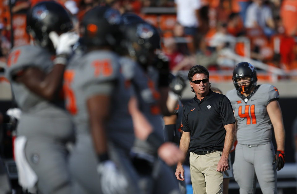 Photo - Oklahoma State head coach Mike Gundy watches players warm up during a college football game between the Oklahoma State Cowboys (OSU) and the Texas Tech Red Raiders at Boone Pickens Stadium in Stillwater, Okla., Saturday, Sept. 22, 2018. Texas Tech won 41-17. Photo by Sarah Phipps, The Oklahoman
