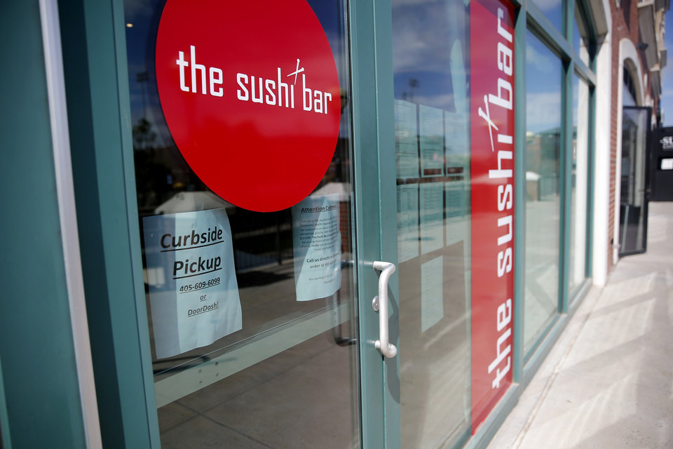 Photo - A sign on the door of the the sushi bar is pictured in Bricktown in Oklahoma City, Wednesday, March 18, 2020. [Sarah Phipps/The Oklahoman]