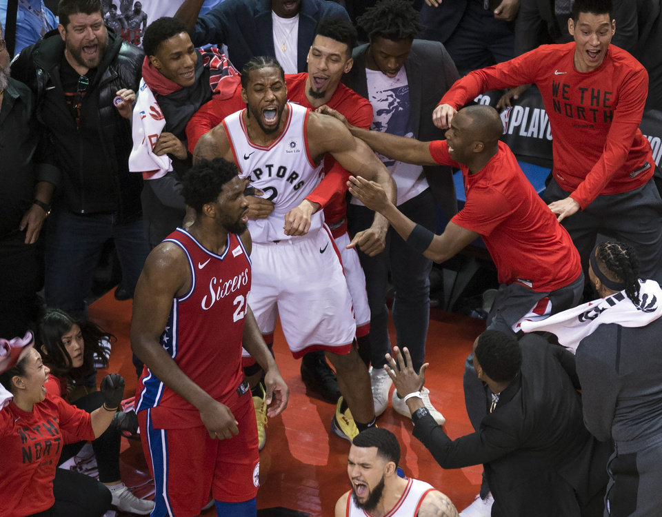Photo - Toronto Raptors forward Kawhi Leonard, center, reacts with teammates after making the game-winning shot as Philadelphia 76ers center Joel Embiid (21) walks away at the end of an NBA Eastern Conference semifinal basketball game, in Toronto, Sunday, May 12, 2019. (Nathan Denette/The Canadian Press via AP)