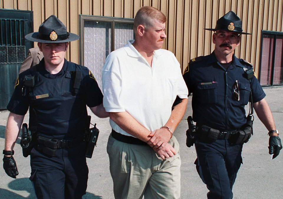 Photo - BRIDGE COLLAPSE, WEBBERS FALLS, I-40, INTERSTATE 40, BARGE, HIT, COLLISION, DEATH, DEATHS, ARKANSAS RIVER, IMPERSONATE, IMPERSONATOR, IMPERSONATION, WILLIAM JAMES CLARK: American fugitive William Clark, center, is escorted from the Ontario Court of Justice in Owen Sound, Ontario, Canada by OPP officers early Monday morning, June 10, 2002. Clark, 29, of Tallapoosa, Mo., was remanded in custody for a week following his court appearance. The American fugitive is wanted for posing as a rescue worker in the aftermath of a deadly bridge collapse in Oklahoma last month. (AP Photo/CP, Owen Sound Sun-Times/James Masters)