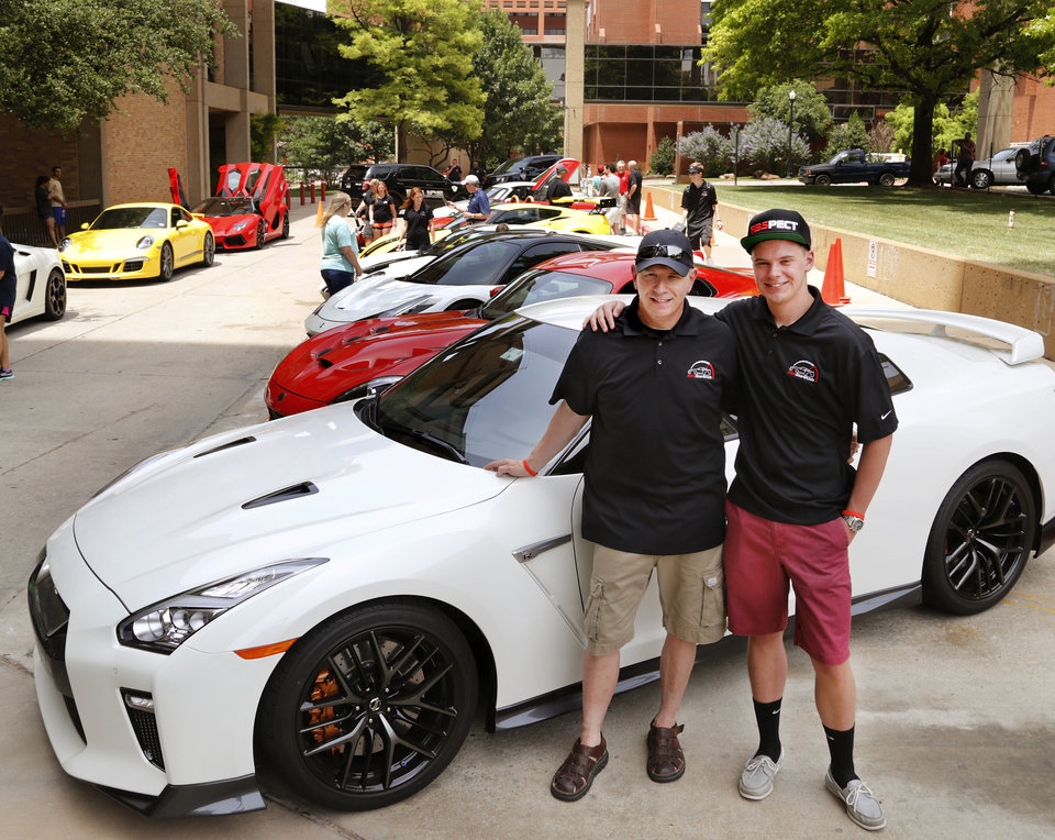 Photo - Eric Wynn, left, with his son, Chance, in front of Chance's car at Saturday's Redline4Kids event at Children's Hospital. Redline4Kids is a new nonprofit that helps connect kids in the hospital with a chance to see cool cars. Photo by Jim Beckel, The Oklahoman